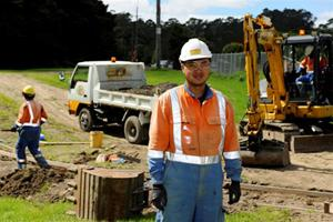 Photo of Michael Lim in front of works on the Bush Road crossing